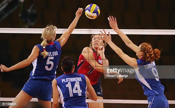Heather Bown of the USA spikes the ball as Lioubov Shashkova and Elizaveta Tishchenko of Russia try to block it as Elena Plotnikova looks on during...