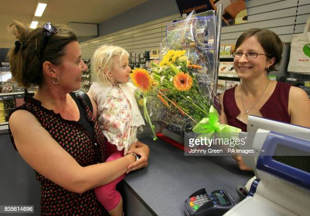 Heather Ikin and her threeyearold daughter Hannah from Westham near Weymouth are handed a bouquet of flowers and two bags of goodies from Wellworths'...