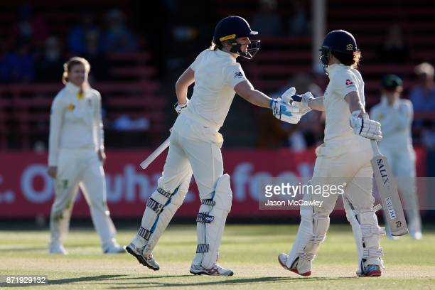 Heather Knight of England is congratulated by Tammy Beaumont after scoring her half centurt during the Women's Test match between Australia and...