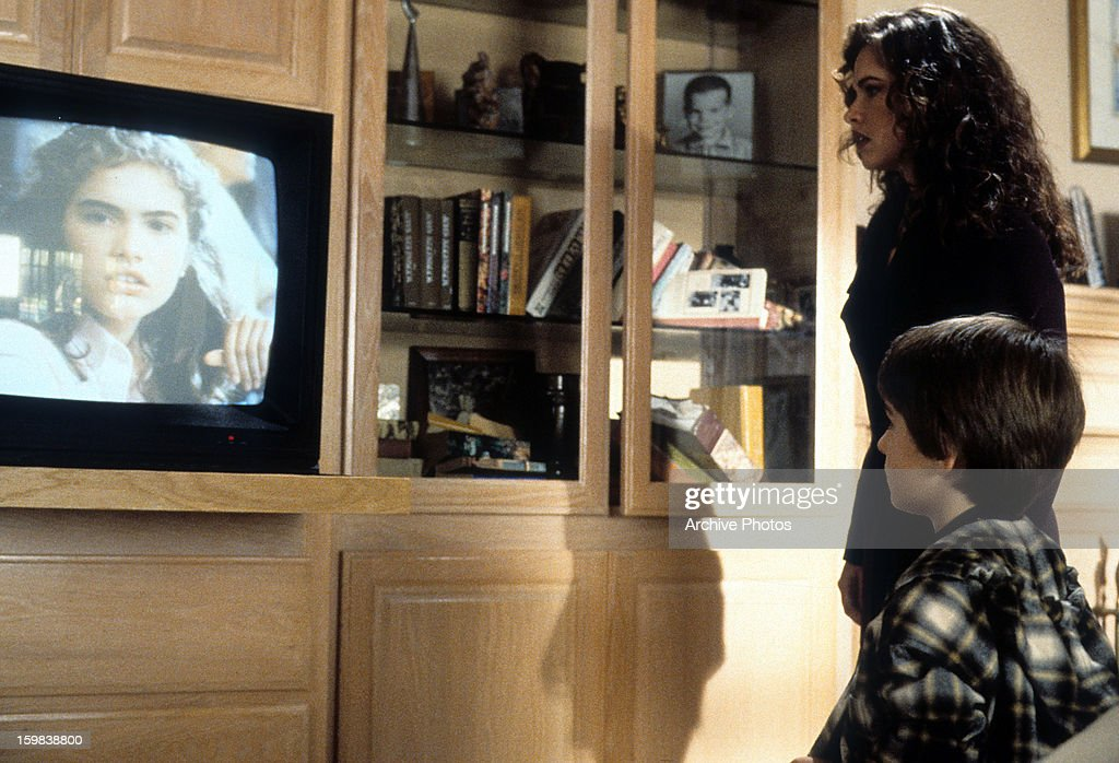 Heather Langenkamp watches tv with Miko Hughes in a scene from the film 'New Nightmare' 1994