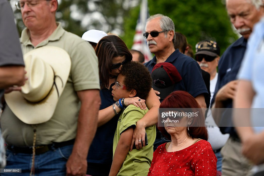 Heather Smith holding and kissing her son Lucian 8, during a prayer at the Memorial Day ceremony, 84th Anniversary of Remembrance at Fort Logan National Cemetery. Her Brother Army CW3 Scott Oswell was killed in action in Iraq. May 30, 2016 in Denver, CO.