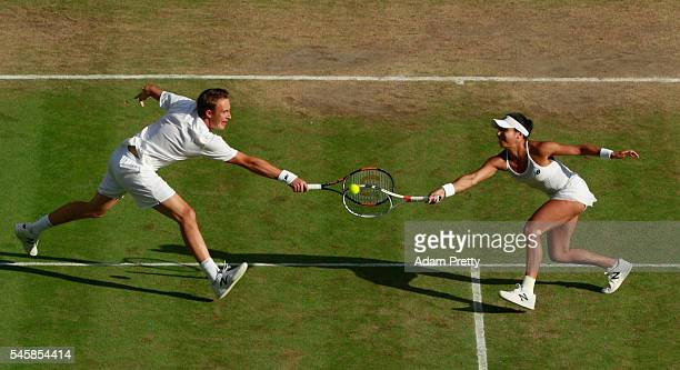 Heather Watson of Great Britain and Henri Kontinen of Finland both stretch to return the ball during the Mixed Doubles Final against Robert Farah of...