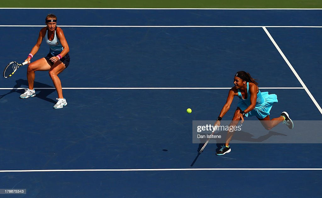 Heather Watson of Great Britain plays a backhand next to ther partner Vera Dushevina of Russia during their women's doubles first round match against...