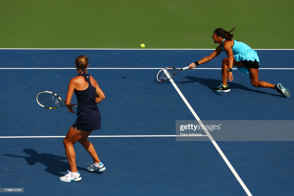 Heather Watson of Great Britain plays a forehand next to ther partner Vera Dushevina of Russia during their women's doubles first round match against...