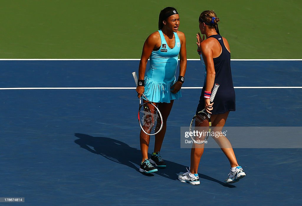Heather Watson of Great Britain talks tactics with her partner Vera Dushevina of Russia during their women's doubles first round match against Sandra...