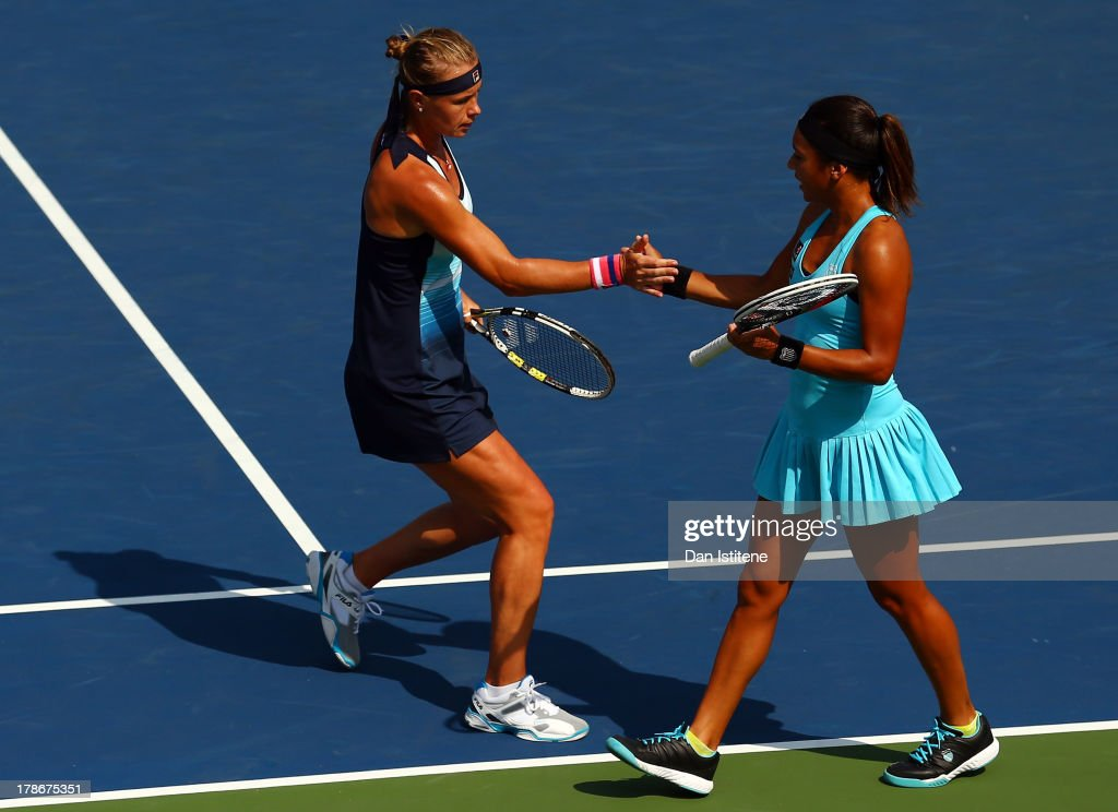 Heather Watson of Great Britain taps hands with her partner Vera Dushevina of Russia during their women's doubles first round match against Sandra...