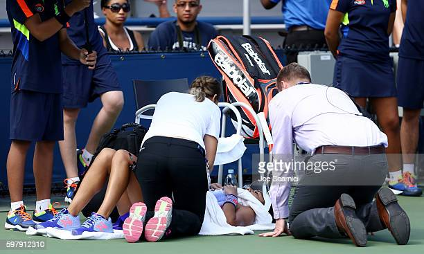 Heather Watson of the United Kingdom is treated by a trainer during her first round Women's Singles maduring her first round Women's Singles match...