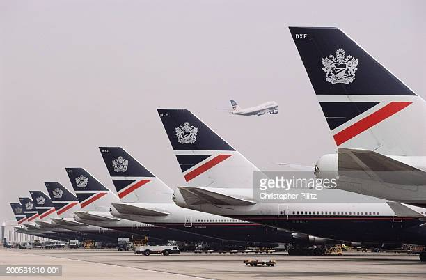 UK, Heathrow Airport, rear of airplanes in row, side view