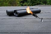 Heating and melting bitumen roofing felt Flat roof installation.