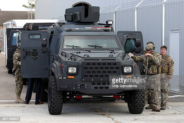 Heavily armed and camouflaged police officers stand by their armored vehicle is parked near a campaign rally for Republican presidential nominee...