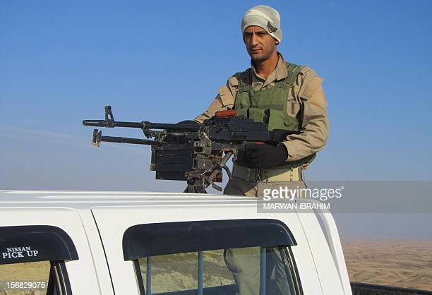Heavily armed Iraqi Kurdish peshmerga fighters hold a post in the mountains between the towns of Tuz Khurmatu and Khanaqin on the border of the...