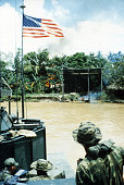 A heavily armed 'Mike' boat carrying members of a US Navy SEAL team departs the site of a Viet Cong fortification on the Bassac River which was...