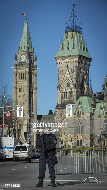 A heavily armed police officer stands watch in front of Parliament on October 23 near the National War Memorial in Ottawa Ontario the day after...