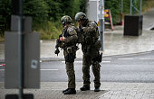 Heavily armed police officers with weapons prepare to respond to a shooting at the Olympia Einkaufzentrum at July 22 2016 in Munich Germany According...