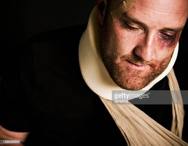 Heavily injured man with neck brace and arm sling