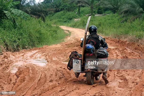 Heavily packed motorbike rider with surfboard riding on bike through mud of dirt road during the rainy season Gabon Central Africa