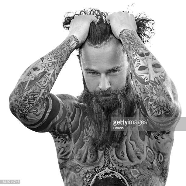 Heavily tattooed bare chested handsome male standing in warrior stance