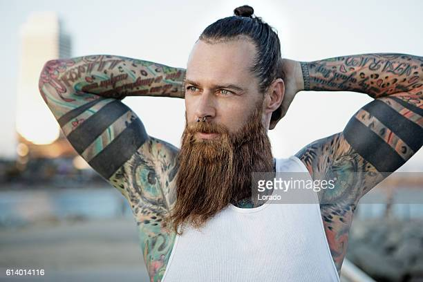 Heavily tattooed bearded athletic alternative man stretching before a workout