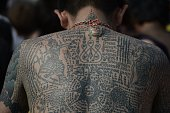 A heavily tattooed Buddhist devotee sits among the crowd during an annual tattoo festival at Wat Bang Phra temple in Nakhon Chaisi west of Bangkok on...