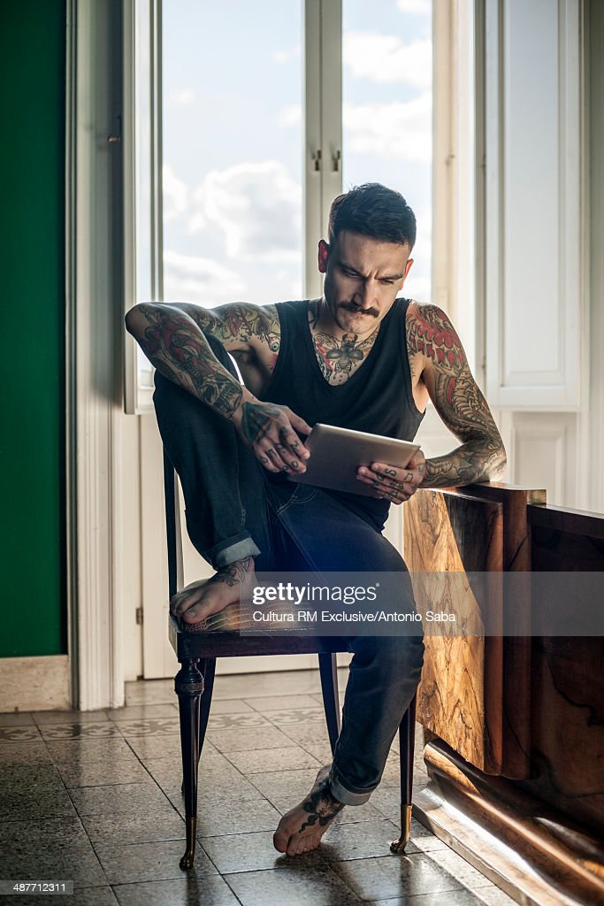 Heavily tattooed man using digital tablet