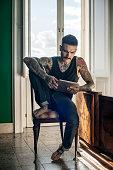 Heavily tattooed man using digital tablet