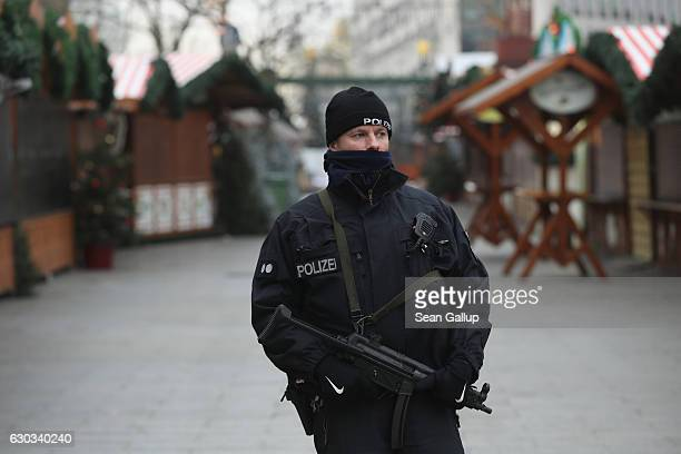 A heavilyarmed policeman stands at the site where two days before a man drove a heavy truck into a Christmas market in an apparent terrorist attack...