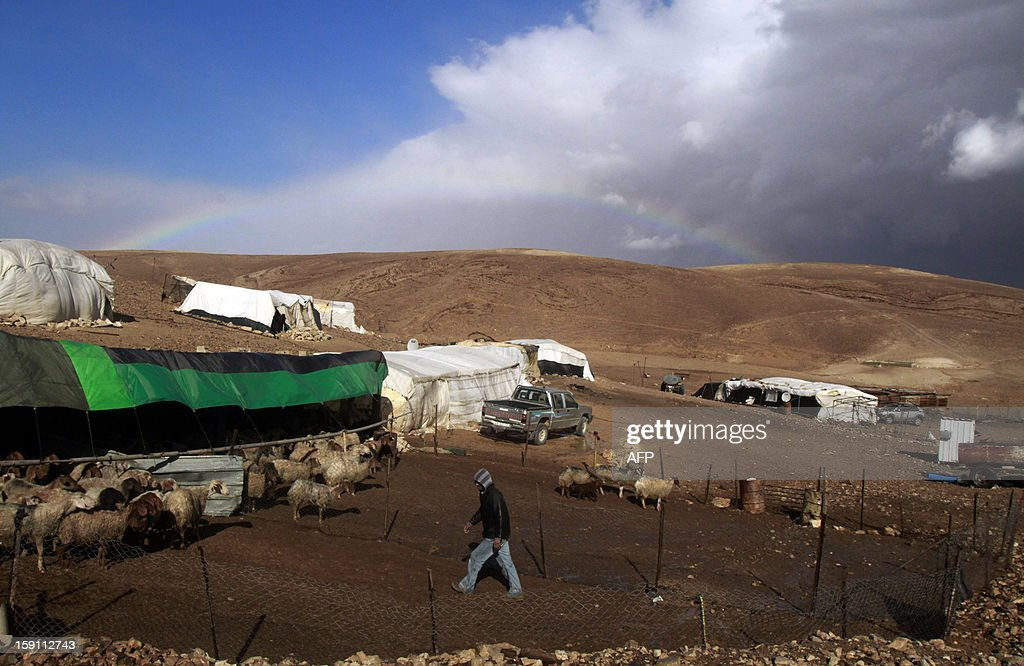 Heavy clouds and a rainbow are seen on the skyline of the the al-Rashaida Bedouin camp in the desert south of the West Bank city of Bethlehem on January 8, 2013. Stormy weather, including high winds and heavy rainfall, lashed Israel and the Palestinian territories, downing powerlines and trees and causing several injuries. AFP PHOTO/MUSA AL SHAER