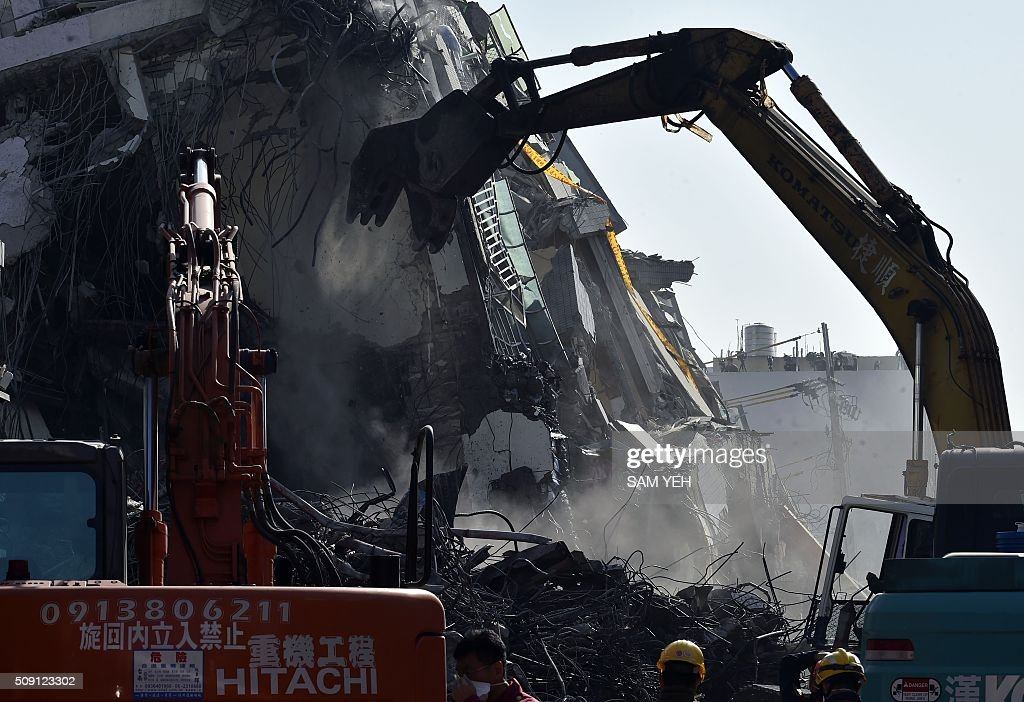 Heavy cranes knock down the collapsed Wei-Kuan complex in Tainan, southern Taiwan, on February 9, 2016. Rescuers deployed heavy machinery in a renewed effort to locate more than 100 people trapped in the rubble of a Taiwan apartment complex felled by an earthquake as the 72-hour 'golden window' for finding survivors passed. AFP PHOTO / Sam Yeh / AFP / SAM YEH