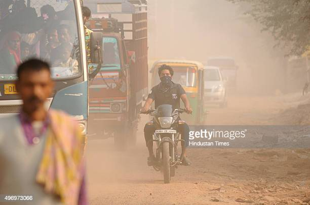 Heavy dust seen as vehicles move on a road making already polluted air more worsen as people commutes through a bad road on November 13 2015 in Noida...