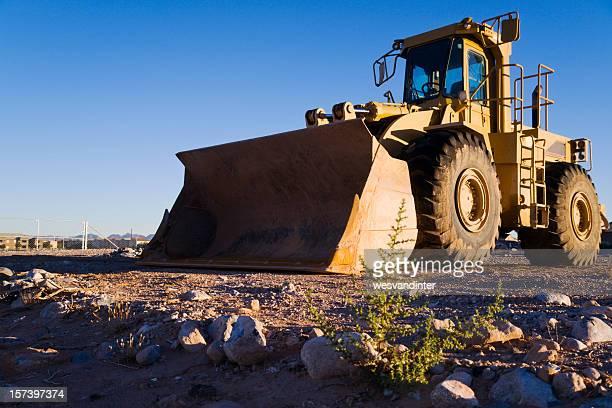 Heavy duty hydraulic front end loader in empty field