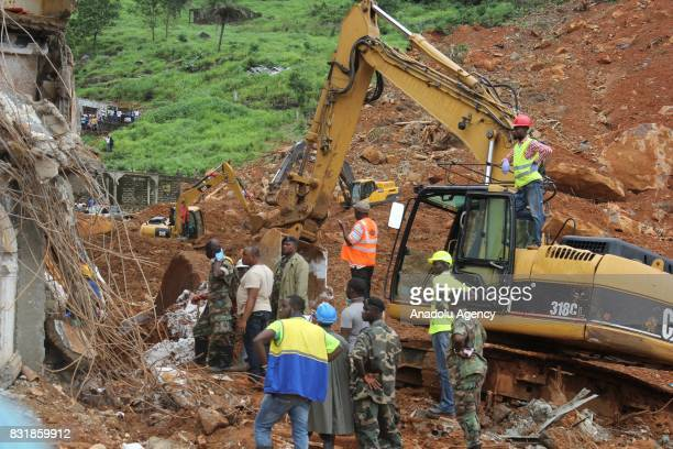 A heavy duty machine and workers remove a wreckage at Regent region of Freetown after landslide struck the capital of the west African state of...