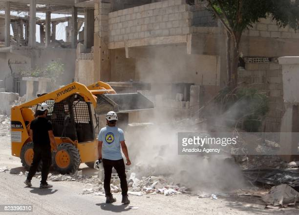 A heavy duty machine lifts the debris of a building as members of an NGO look on in Daraa Syria on July 27 2017 Syrians started to return their homes...
