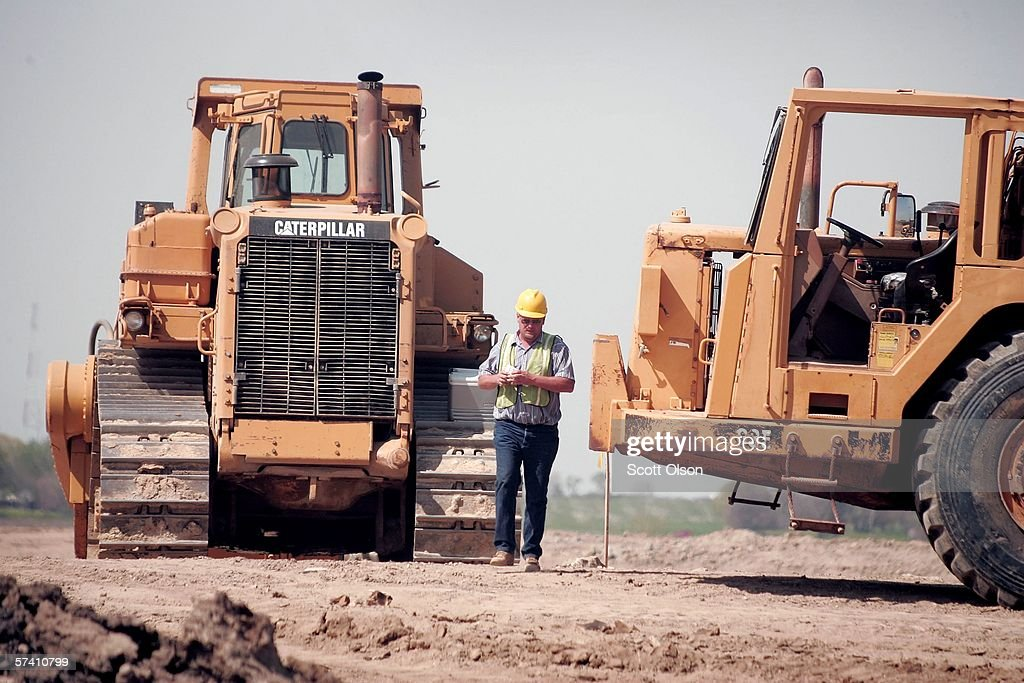 A heavy equipment operator walks between Caterpillar earth moving equipment at a road construction site on April 24 2006 near Joliet Illinois Heavy...