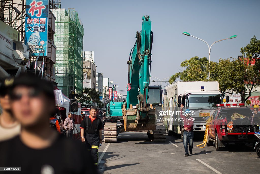 A heavy excavator vehicle is driven towards a collapsed building in the southern Taiwanese city of Tainan on February 7, 2016, following a strong 6.4-magnitude earthquake that struck early on February 6. Rescuers raced on February 7 to free more than 120 people buried under the rubble of an apartment complex felled by an earthquake in southern Taiwan that left 24 confirmed dead, as an investigation began into the collapse. AFP PHOTO / ANTHONY WALLACE / AFP / ANTHONY WALLACE