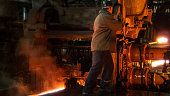 Heavy Industry Worker Working Hard on Machine in Foundry. Rough Industrial Environment. Wide Shot.