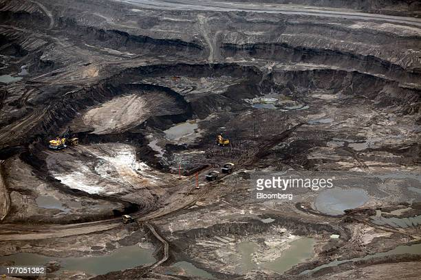 Heavy machinery operates at a Suncor Energy Inc oil sands mining operation near Fort McMurray Alberta Canada on Tuesday Aug 13 2013 Canadian oil...