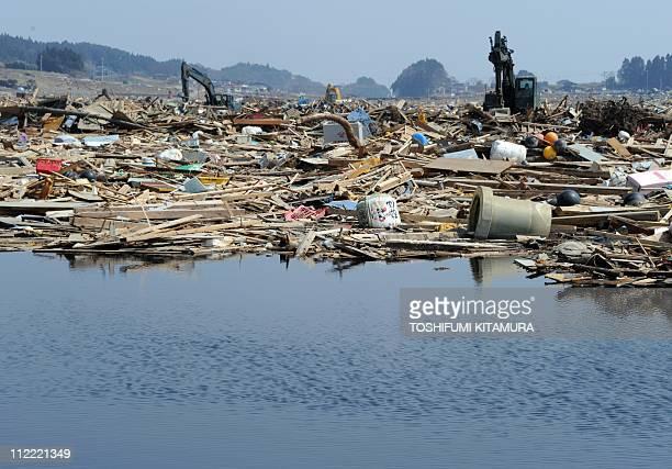 Heavy machinery removes March 11 tsunami debris covering rice fields at the Otomo area in Rikuzentakata city Iwate prefecture on April 15 2011...