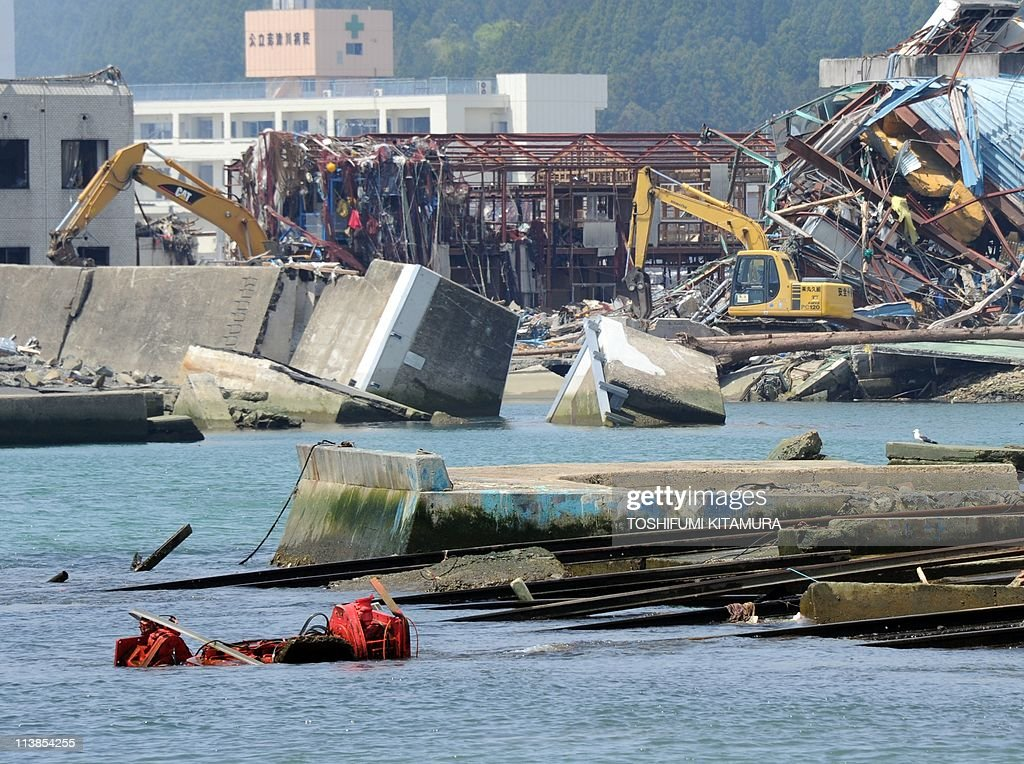 Heavy machinery removes the rubble beside the collapsed breakwater at the tsunami-devastated town of Minamisanriku, Miyagi prefecture on May 9, 2011. Japan's largest earthquake of magnitude 9.0 hit the northeastern region on March 11, releasing massive tsunami to destroy the Pacific coast of northern Japan which killed nearly 15,000 people with more than 10,000 still missing.