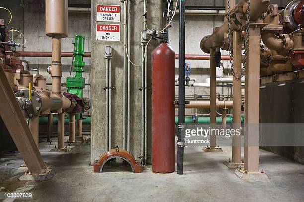 Heavy machinery with compressed gas cylinder in a sewage treatment plant