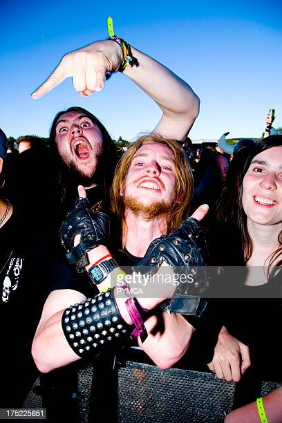 Heavy Metal fans in a crowd gesturing to camera Bloodstock Outdoor festival UK 16/07/06