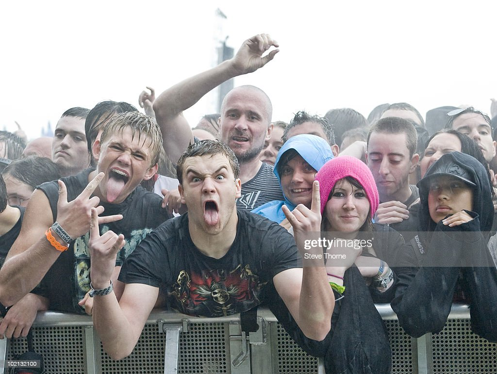 Heavy metal fans in the crowd cheering in the rain while watching Motorhead perform on stage on the last day of Download Festival at Donington Park on June 13, 2010 in Castle Donington, England.