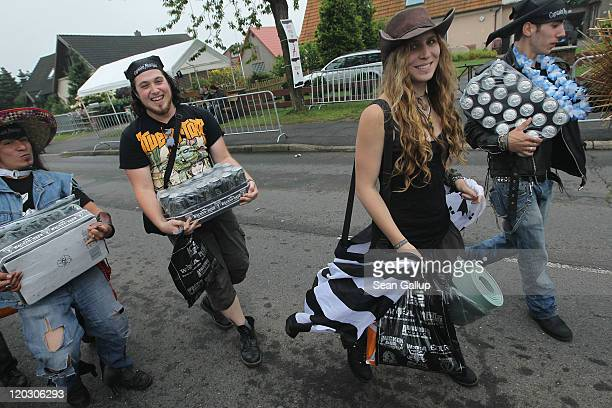 Heavy metal music fans carrying ample supplies of beer walk along the main street on the first day of the Wacken Open Air heavy metal music fest on...