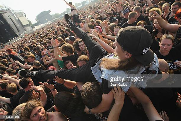 Heavy metal music fans hold aloft a fellow fan during a performance by thrash band FreiWild on the first day of the Wacken Open Air heavy metal music...