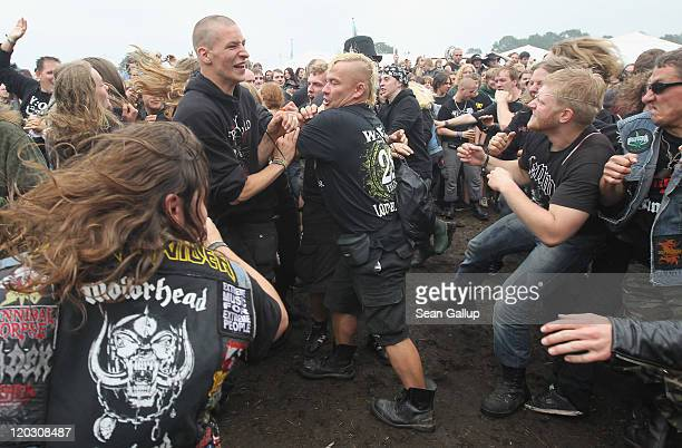 Heavy metal music fans slam dance during a performance at one of the smaller stages on the first day of the Wacken Open Air heavy metal music fest on...