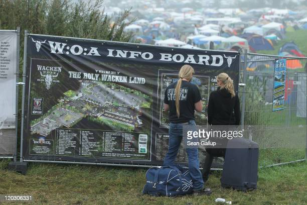 Heavy metal music fans stand in front of a map upon their arrival with their suitcases on the first day of the Wacken Open Air heavy metal music fest...