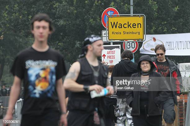 Heavy metal music fans walk along the main street on the first day of the Wacken Open Air heavy metal music fest on August 4 2011 in Wacken Germany...