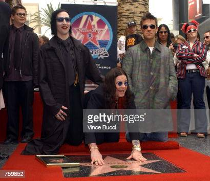 Heavy metal music performer Ozzy Osbourne poses with musicians Marilyn Manson and Robbie Williams during the ceremony honoring him with a star on the...