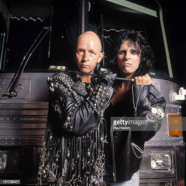 Heavy metal singers Rob Halford and Alice Cooper pose in front of a tourbus early 1990s