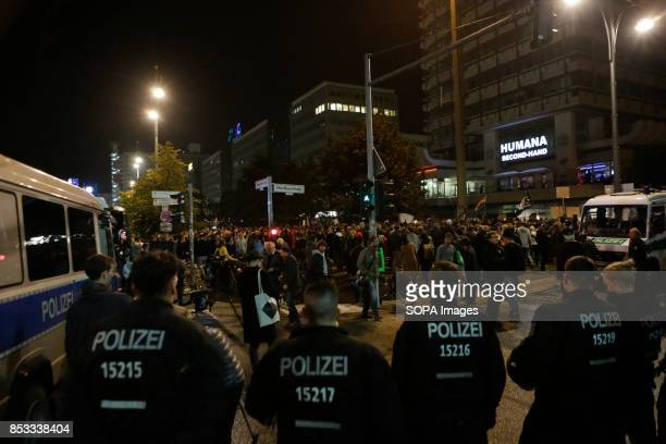 A heavy police presence watches the protesters from the back Hundreds of protesters gathered outside a club near the central Alexanderplatz in Berlin...