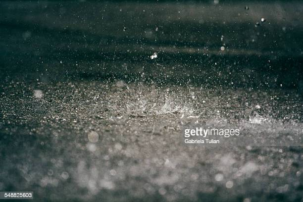 Heavy rain drops on asphalt